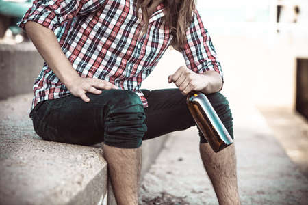 Man depressed with wine bottle sitting on sea shore outdoor. People abuse and alcoholism problems