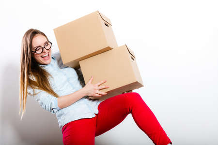 Happy woman moving in carrying cartons boxes. Young girl arranging interior and unpacking at new apartment house home. Stock Photo