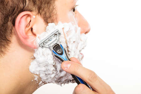 Man shaving using razor with cream foam. Guy removing face beard hair. Skin care and hygiene.