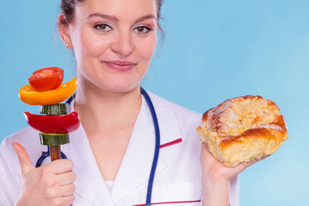 eating right: Happy dietitian nutritionist with sweet roll bun and vegetables like cucumber, tomato and pepper. Woman holding comparing junk and healthy food. Right eating nutrition concept.