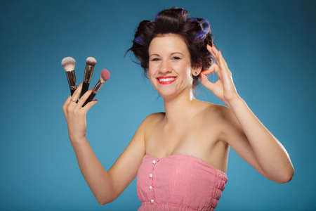 hair rollers: Cosmetic beauty procedures and makeover concept. Woman in hair rollers holding makeup brushes set making ok sign gesture on blue