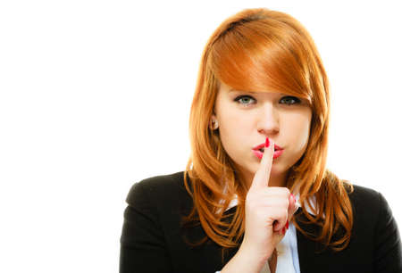 Business woman redhaired girl asking for silence or secrecy with finger on lips hush hand gesture. Isolated Stock Photo
