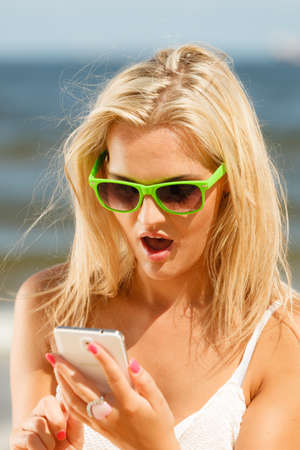 updated: Shocked young girl on beach with sunglasses using her mobile phone to be updated. Social network and internet concept.