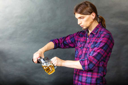 taphouse: Alcohol liquor drinking relax party concept. Tapster fills stein from bottle. Young male bartender empties beer into glass. Stock Photo