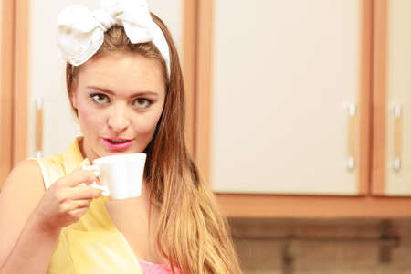 Pretty pin up girl with hairband bow drinking tea or coffee at home. Gorgeous young retro woman with hot beverage relaxing in kitchen. Stock Photo