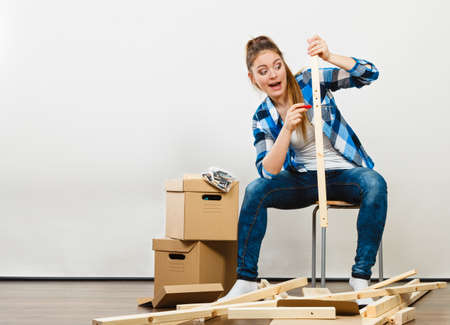 Woman moving into new apartment house assembling furniture with screwdriver. Young girl sitting on chair arranging interior and unpacking boxes.