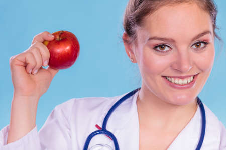 promoting: Happy dietitian nutritionist holding apple. Woman promoting healthy food fruit. Right eating nutrition and slimming concept.