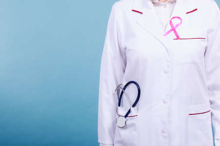 breast pocket: Women fight for health. Breast cancer tumor concept. Pink ribbon on white medical apron uniform and blue stethoscope in pocket.