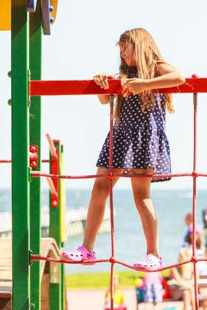 enjoyable: Time for fun. Summer holidays concept. Little funny girl having fun on playground. Child climbing. Enjoyable playful kid outdoors.