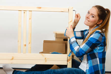 enthusiast: Woman assembling wooden furniture using hex key. DIY enthusiast. Young girl doing home improvement.