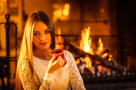 energizing: Woman drinking cup of coffee relaxing at fireplace. Young girl with hot beverage heating warming up. Winter at home. Stock Photo
