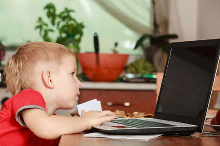 early education: Technology and early education. Child use laptop for fun and learning. Boy sit alone with computer on table indoors wear red shirt. Stock Photo