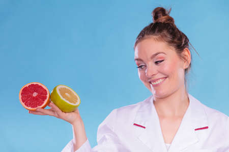 dietitian: Happy dietitian nutritionist holding grapefruits. Woman promoting healthy food fruit. Right eating nutrition and slimming concept. Stock Photo