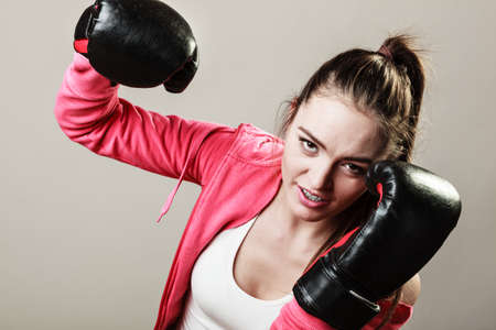 the emancipation: Training, boxing and exercises. Women lifestyle concept. Fit girl with gloves on grey background in studio.