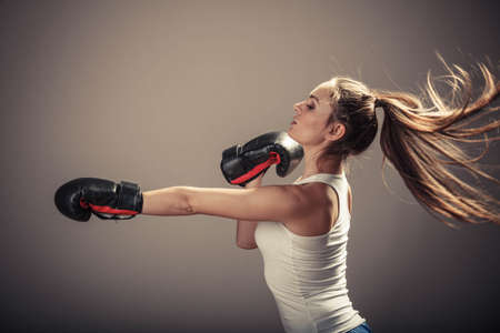 intimidating: Energy fighting boxing with opponent. Sports and bodybuilding. Strong young woman punch enemy. Girl with ponytail wear white tank top and boxing gloves side view.