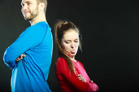 offended: Offended young couple standing back to back after argument quarrel. Woman sticking out tongue. Disagreement in relationship.