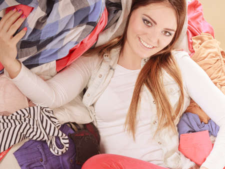 messy clothes: Happy woman lying on sofa couch in messy living room. Young girl surrounded by many stack of clothes. Disorder and mess at home. Stock Photo