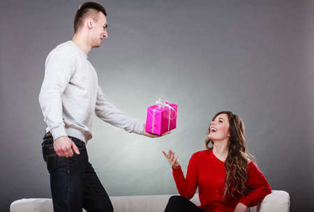 gifting: Couple and holiday concept. Handsome man surprising cheerful woman with gift box