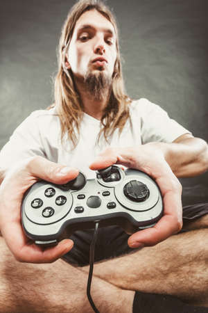 dependency: Lifestyle of young people. Student man spending time on playing games videogames console. Long haired guy focus on gaming. Stock Photo