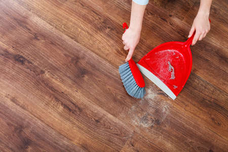 closeup cleaning woman sweeping wooden floor with red small whisk broom and