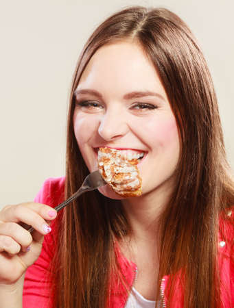 caloric: Smiling woman eating cake. Caloric food.