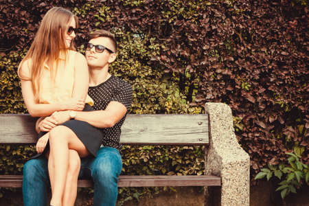 Love romance flirt dating concept. Affectionate couple sitting on bench. Young girl sitting on her boy lap.