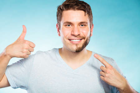 Portrait of happy man with half shaved face beard hair. Smiling handsome guy on blue showing thumb up gesture. Skin care and hygiene.