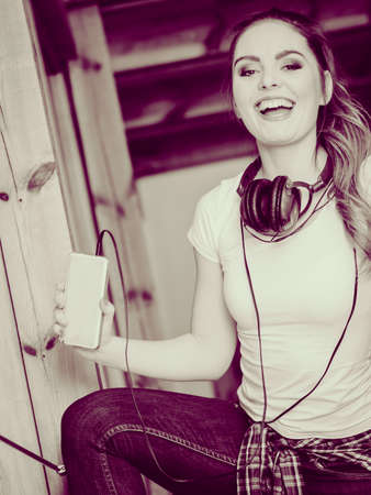 dance time: Hobby music expression and free time. Young girl listen music on phone dance indoors have fun hold smartphone.