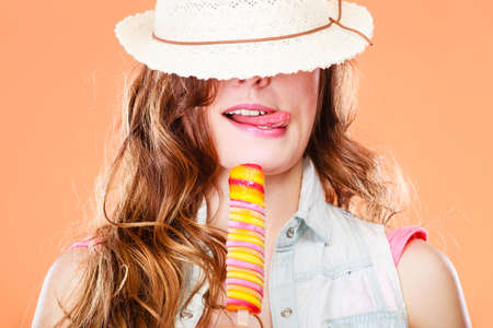Summer vacation happiness concept. Funny cheerful woman covering eyes with straw hat eating ice cream orange background