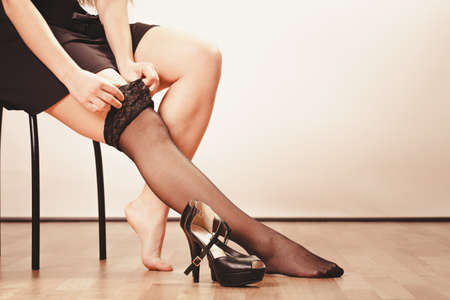 sexualidad: La belleza y la sexualidad de las mujeres. Modelo de la mujer atractiva que desgasta parte del cuerpo en forma de bragas negras medias de los pantalones. Piernas femeninas con tacones altos.
