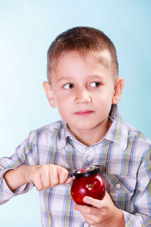 early education: Early education nature and biology discovery. Little boy examine fruit apple with magnifying glass.