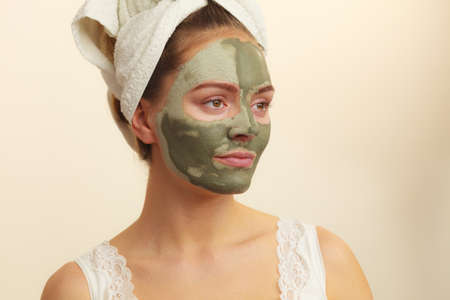 mud girl: Skin care. Woman face with green clay mud mask. Girl taking care of oily complexion. Beauty treatment. Stock Photo
