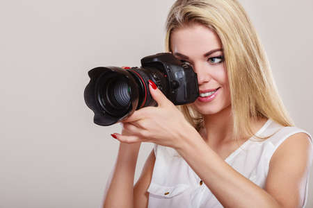 Photographer girl shooting images. Attractive blonde woman taking photo with camera. Stock Photo