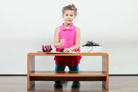 elementary age: Little girl create composition in the classroom. Being creative in elementary age Stock Photo