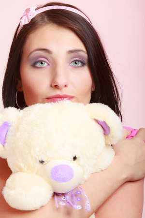 infantile: Portrait of childish young woman with headband holding toy. Infantile girl hugging teddy bear on pink. Longing for childhood. Studio shot. Stock Photo