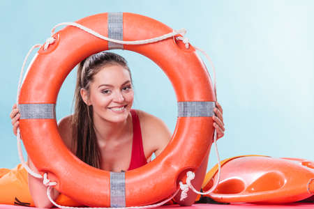 savers: Lifeguard with ring buoy lifebuoy. Woman girl supervising swimming pool water on blue. Accident prevention. Stock Photo