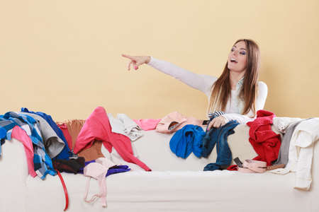habitacion desordenada: Happy woman behind sofa couch in messy living room pointing at empty blank copy space. Young girl surrounded by many stack of clothes. Disorder and mess at home.