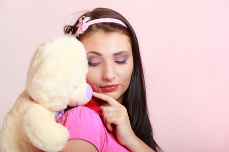 longing: Portrait of childish young woman with headband holding toy. Infantile girl hugging teddy bear on pink. Longing for childhood. Studio shot. Stock Photo