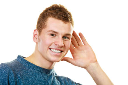 Gossip. Young man holding hand to ear listening isolated on white background