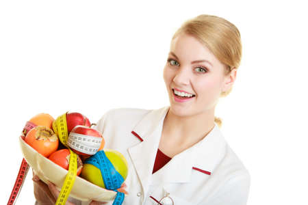 Woman in lab coat holding fruits and measure tapes isolated. Doctor dietitian with healthy food. Diet.