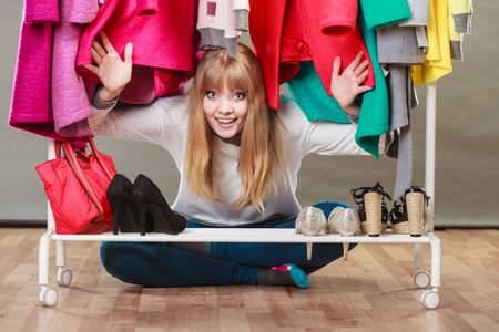 Pretty woman sitting on the floor under clothing from wardrobe. Young happy undecided shopper girl bought new clothes. Shopaholic concept. Stock Photo