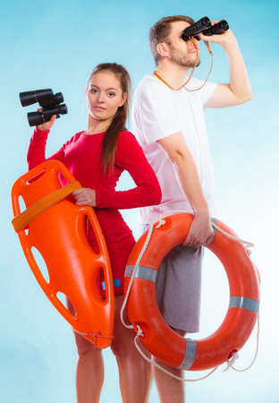 Accident prevention and water rescue. Young man and woman lifeguards on duty looking through binoculars keeping buoy lifesaver equipment on blue Stock Photo