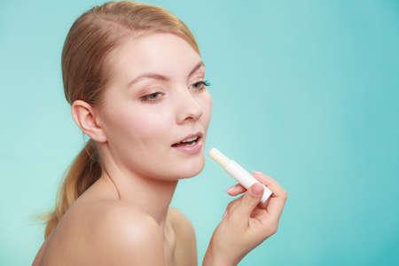 Female putting applying lip balm moisturizing balsam. Girl taking care of lips. Skincare. Banco de Imagens