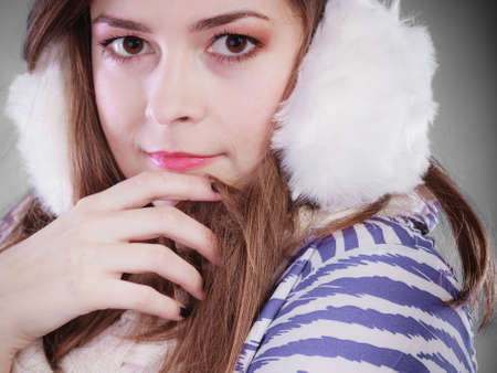 earmuff: Teenage girl wearing fluffy white earmuff in winter fashion, freezing cold time. Stock Photo