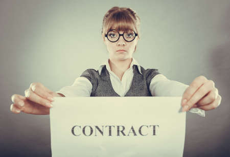 unsatisfied: Business, documents and legal concept - serious unhappy businesswoman showing crumpled contract Stock Photo