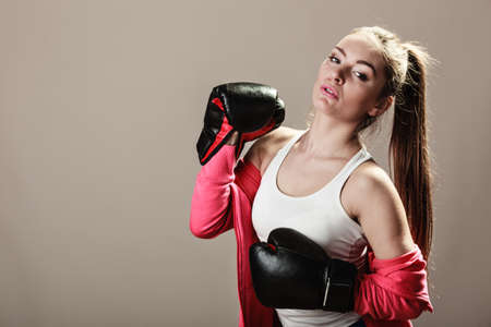 emancipation: Feminist and emancipation idea. Woman in male occupation, training, boxing. Fit female fitness girl doing exercise on grey background.