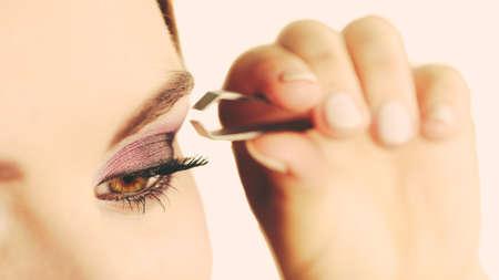 pluck: Make up and cosmetics. Woman plucking eyebrows depilating with tweezers. Attractive girl tweezing eyebrows