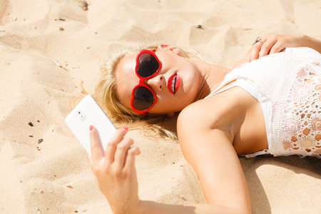 Technology and summer. Woman in red heart shaped sunglasses texting on mobile phone, using smartphone reading sms or taking photo of herself on beach