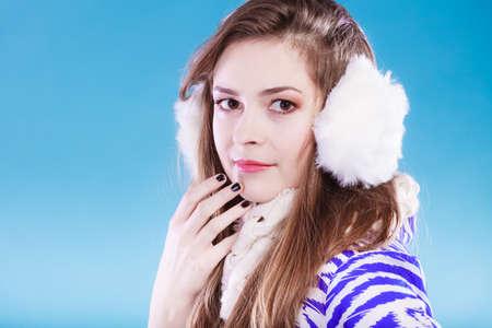 Teenage girl wearing fluffy white earmuff in winter fashion, cold time. Stock Photo