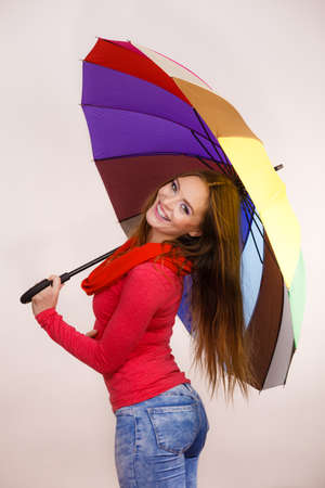 forecasting: Woman fashionable rainy smiling girl in red clothing standing under colorful umbrella having fun. Meteorology, forecasting and weather season concept